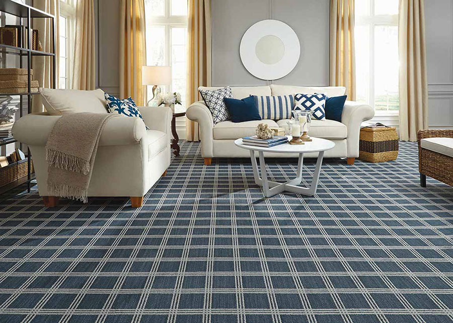 Living room with white sofas covered in blue throw pillows, and a white coffee table on blue and white tiled carpet.