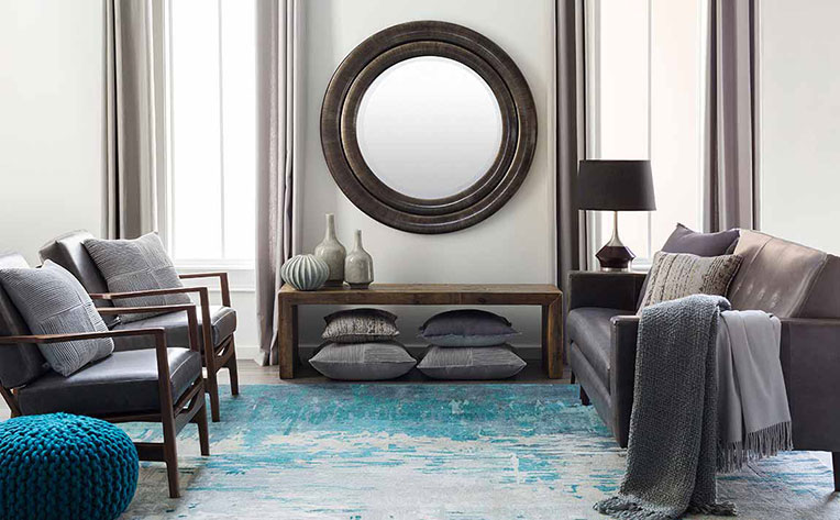 Living room with grey chairs, sofa and blue ottoman on a blue rug.